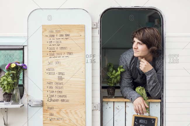 Thoughtful male owner looking out through food truck window