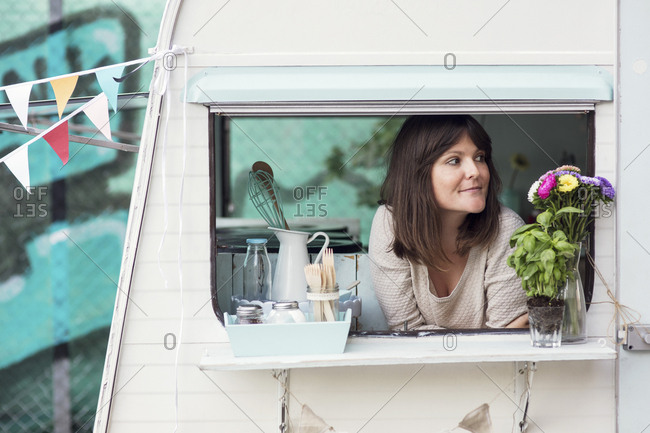 Thoughtful female owner looking out through food truck window