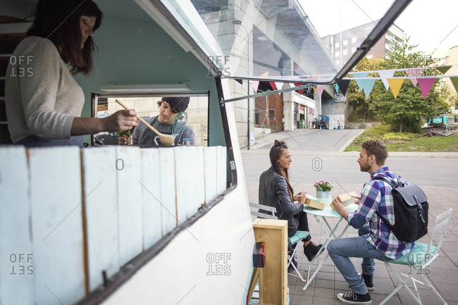 Owners working at food truck while customers sitting in background