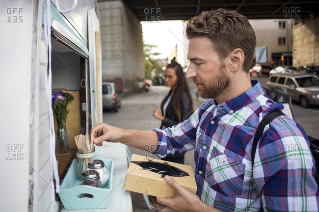 Male customer removing fork from container outside food truck with woman in background