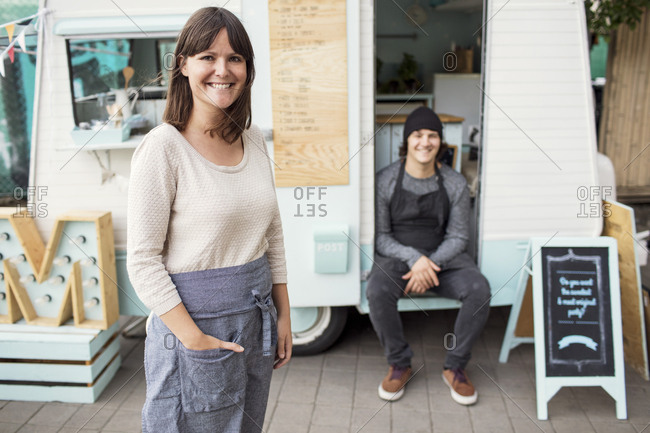Portrait of happy female owner standing on street while colleague sitting in food truck