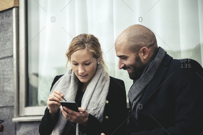 Smiling businesswoman looking at businesswoman using smart phone against window