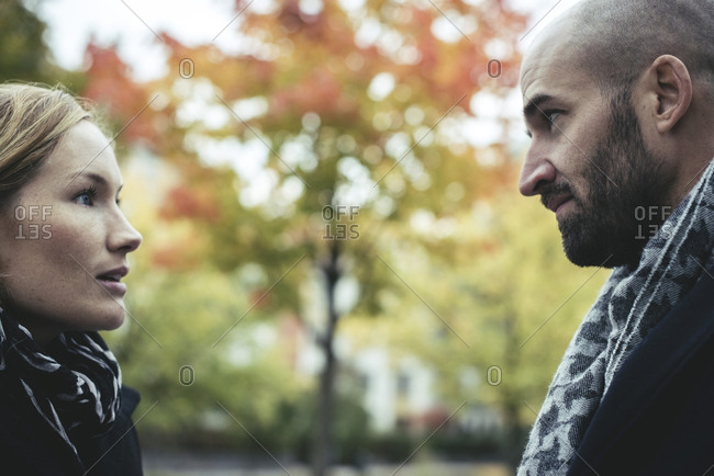 Profile shot of businesswoman talking with businessman outdoors