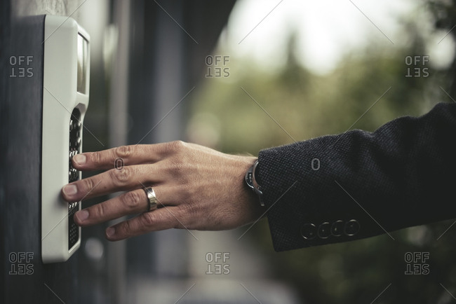 Cropped image of businessman's hand entering security code