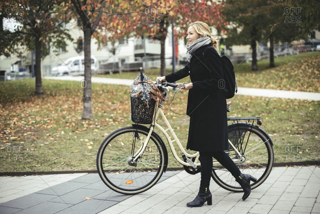Full length side view of businesswoman with bicycle walking on footpath during autumn