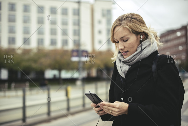 Mid adult businesswoman listening music through smart phone at tram station