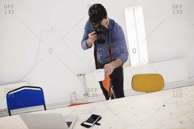 Blogger photographing coffee cup at desk in creative office