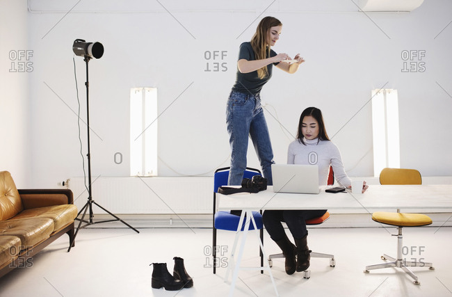 Blogger photographing colleague using laptop at desk in office
