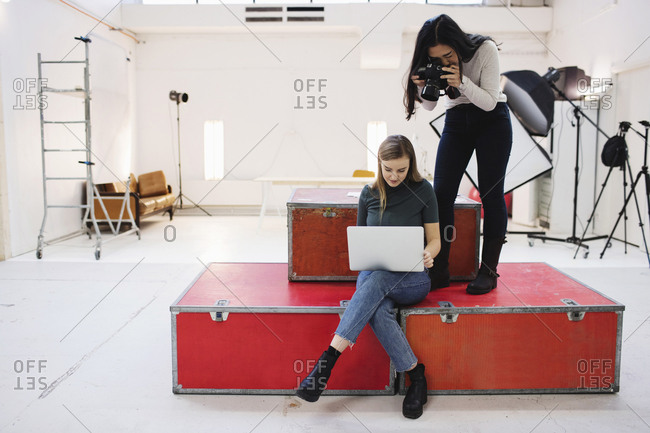 Blogger photographing female colleague using laptop in creative office