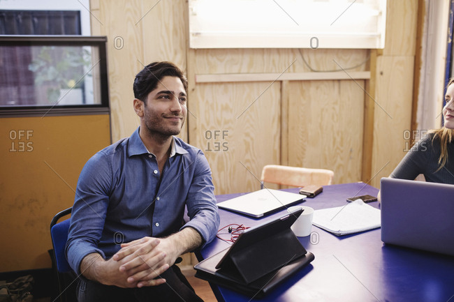 Smiling young man looking away while sitting at desk in office
