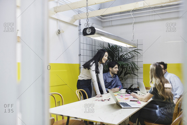 Four people discussing in board room at creative office