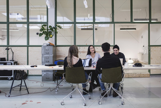 Four people discussing at desk in creative office