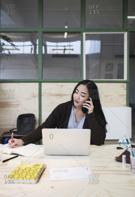 Woman using smart phone at desk in creative office