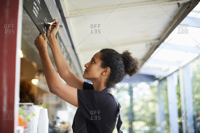 Side view of young waitress writing on menu at cafe