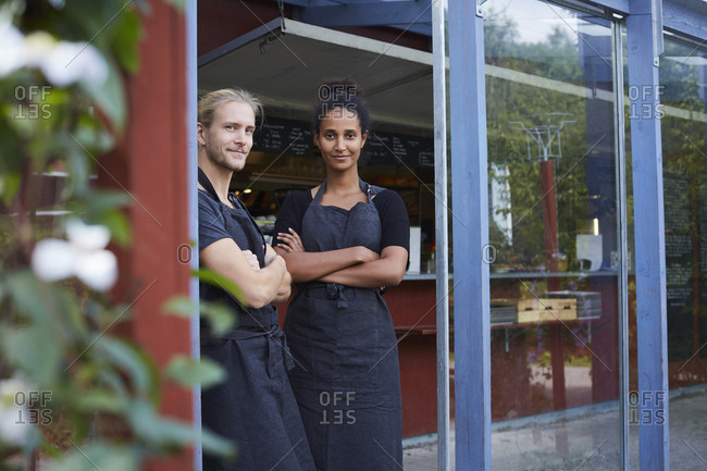 Portrait of confident coworkers standing at cafe entrance