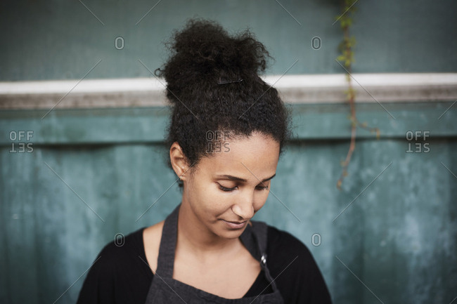 Young female gardener looking down at yard