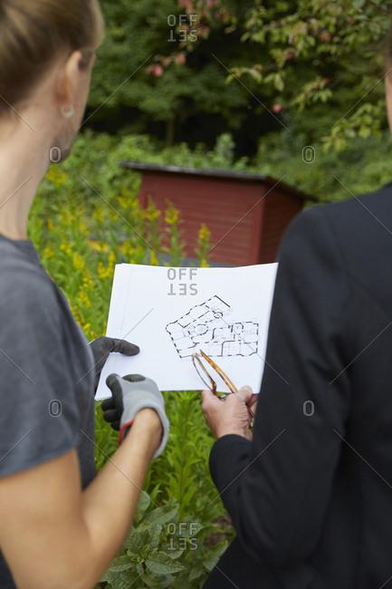 Cropped image of garden architects analyzing blueprint