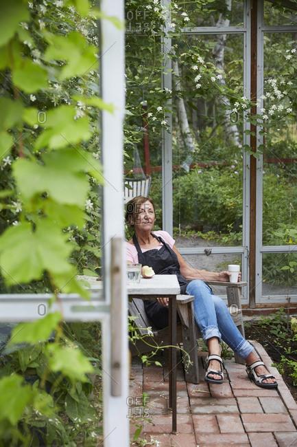 Female gardener resting in glass house