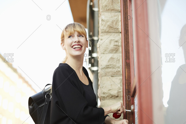 Low angle view of smiling businesswoman unlocking office door with key