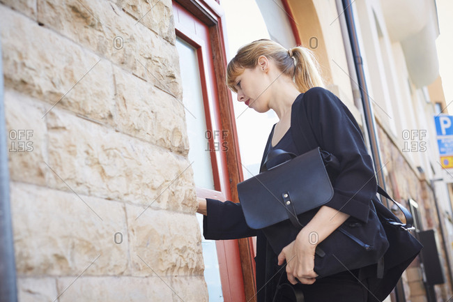 Low angle view of businesswoman with bags entering into office