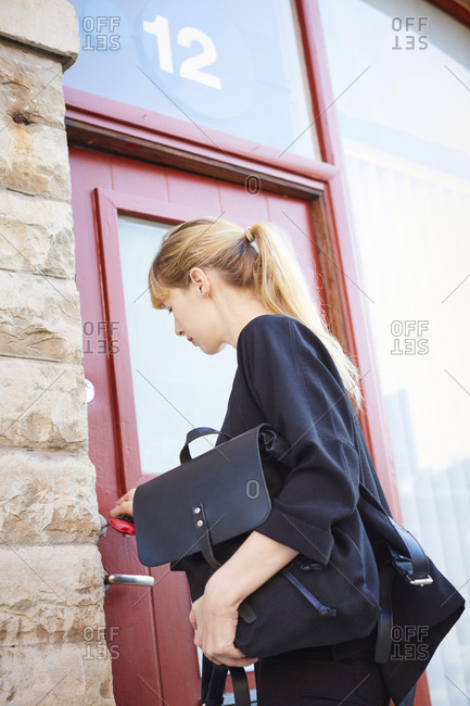 Mid adult businesswoman carrying bags while unlocking office door with key
