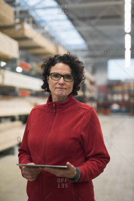 Portrait of confident female customer holding digital tablet while standing in hardware store warehouse