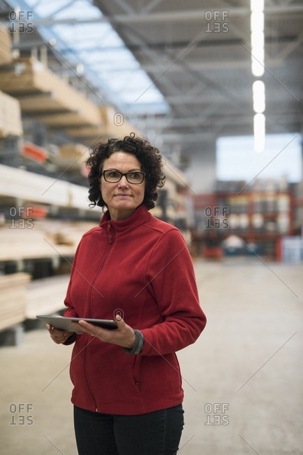 Thoughtful female customer holding digital tablet while standing in hardware store warehouse