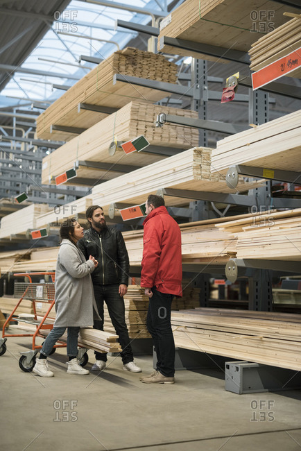 Customers and salesman standing by wooden planks on shelves in hardware store