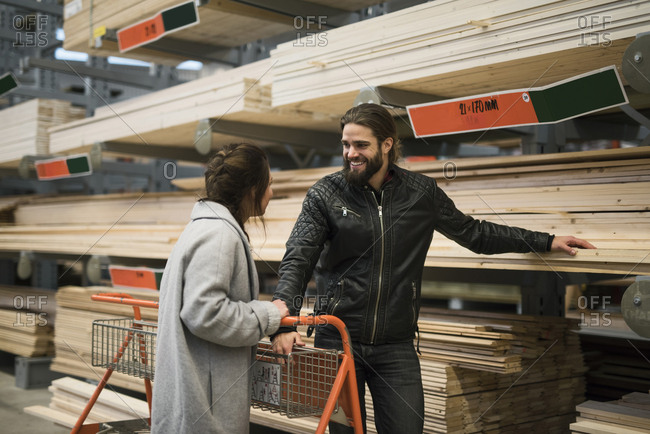 Smiling man standing with woman by wooden planks on shelves at hardware store