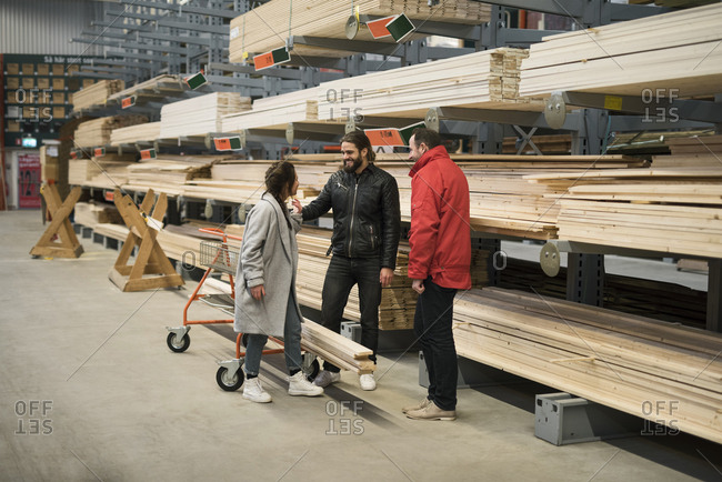 Customers and salesman standing by wooden planks on shelves in hardware store warehouse