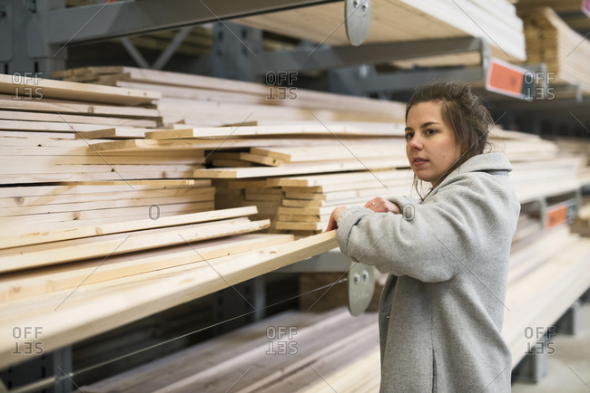 Side view of female customer holding wooden plank in hardware store