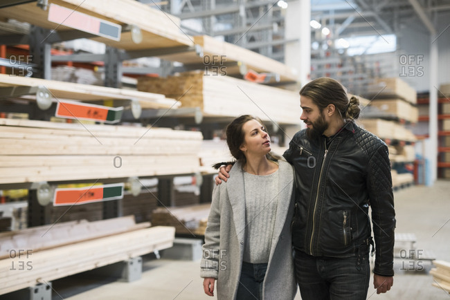 Couple looking at each other while walking in hardware store warehouse