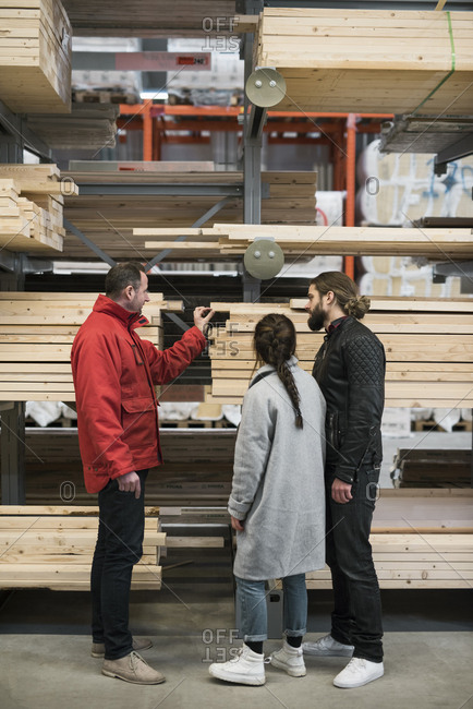 Salesman assisting couple in buying wooden planks in hardware store