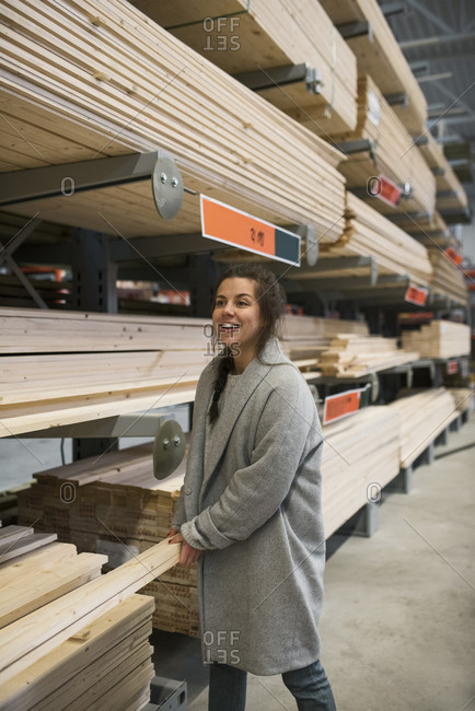 Happy female customer carrying wooden planks by shelves in hardware store