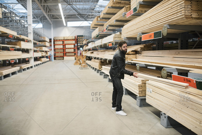 Side view of male customer holding wooden planks by shelves in hardware store
