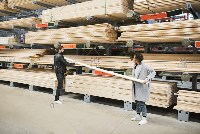 Full length of couple examining wooden plank while standing by shelves at hardware store