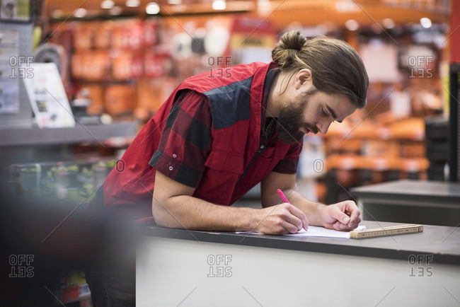 Salesman writing in book at hardware store