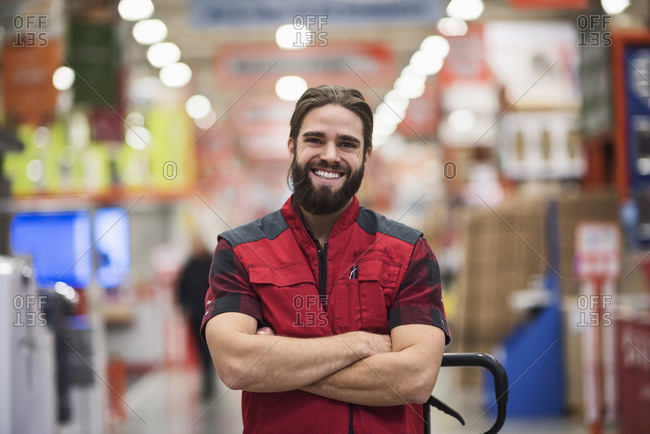 Portrait of happy salesman standing arms crossed at hardware store