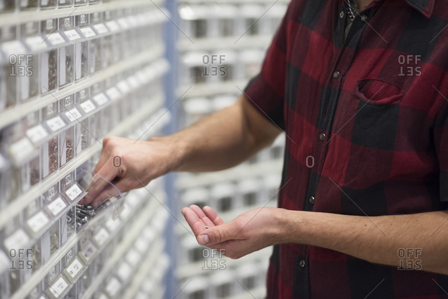 Midsection of male customer choosing nails at hardware store
