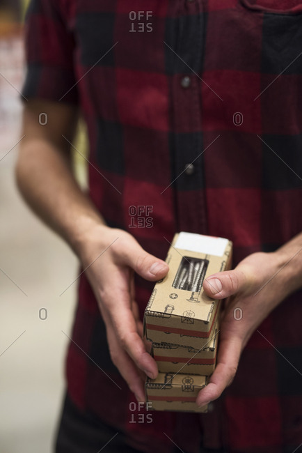 Midsection of male customer holding screw boxes in store