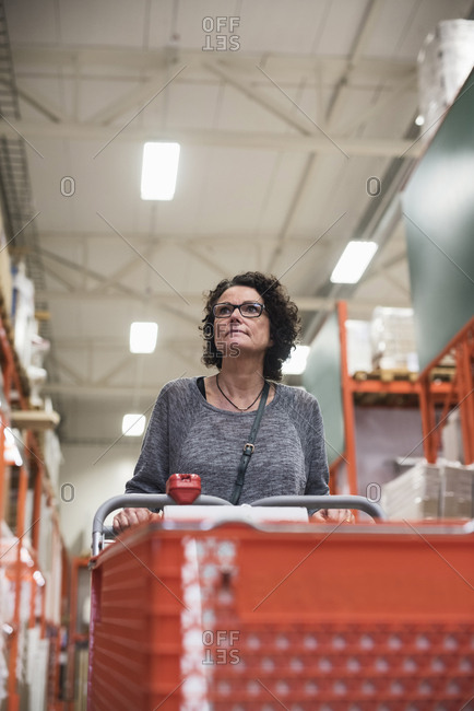 Customer looking away while holding shopping cart in hardware store