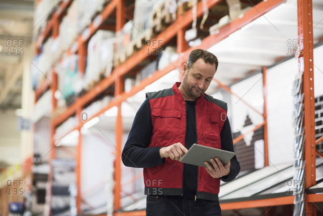 Salesman using digital tablet while standing by shelf in hardware store