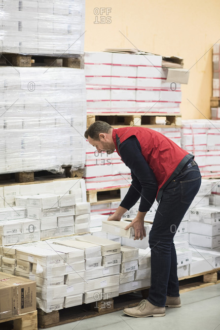 Side view of salesman arranging packages in hardware store