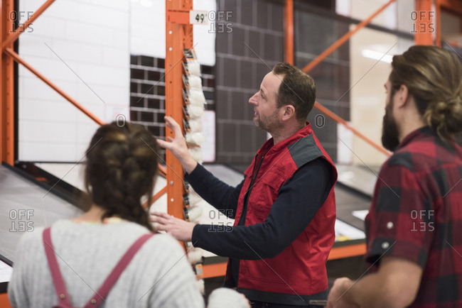 Salesman assisting couple in choosing tile at hardware store