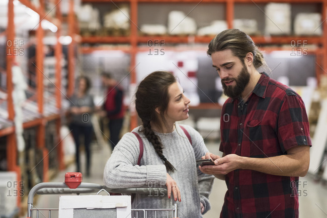 Couple using smart phone in hardware store