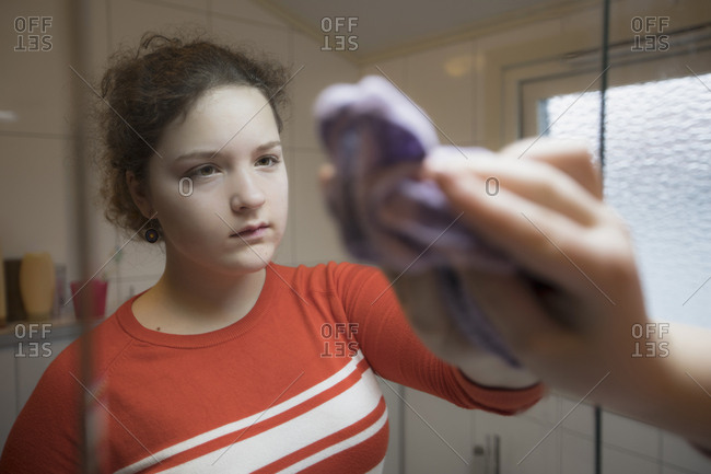Reflection of girl cleaning mirror in bathroom
