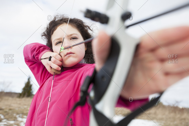 Determined girl practicing archery on field