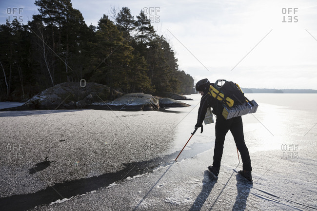 Full length of mature man dipping hiking pole in water while standing on frozen lake
