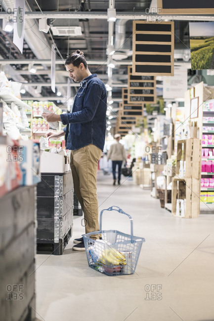 Side view of man buying groceries in supermarket