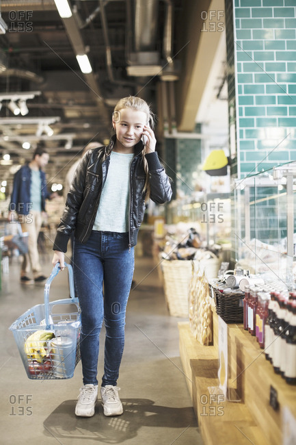 Girl using smart phone while standing in organic groceries store